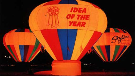 Hot air shaped advertising balloons lit up at night